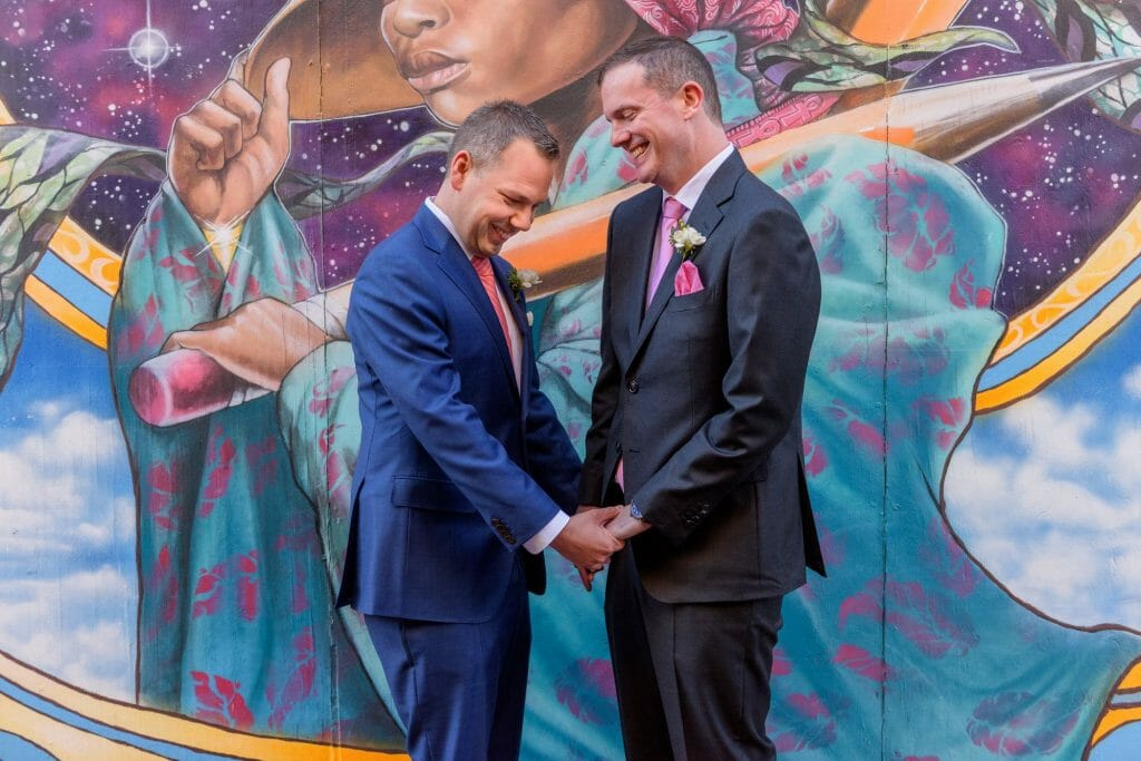 Long View Gallery DC LGBT Wedding Portraits Two Grooms in Blagden Alley with Mural Artwork by Aniekan Udofia