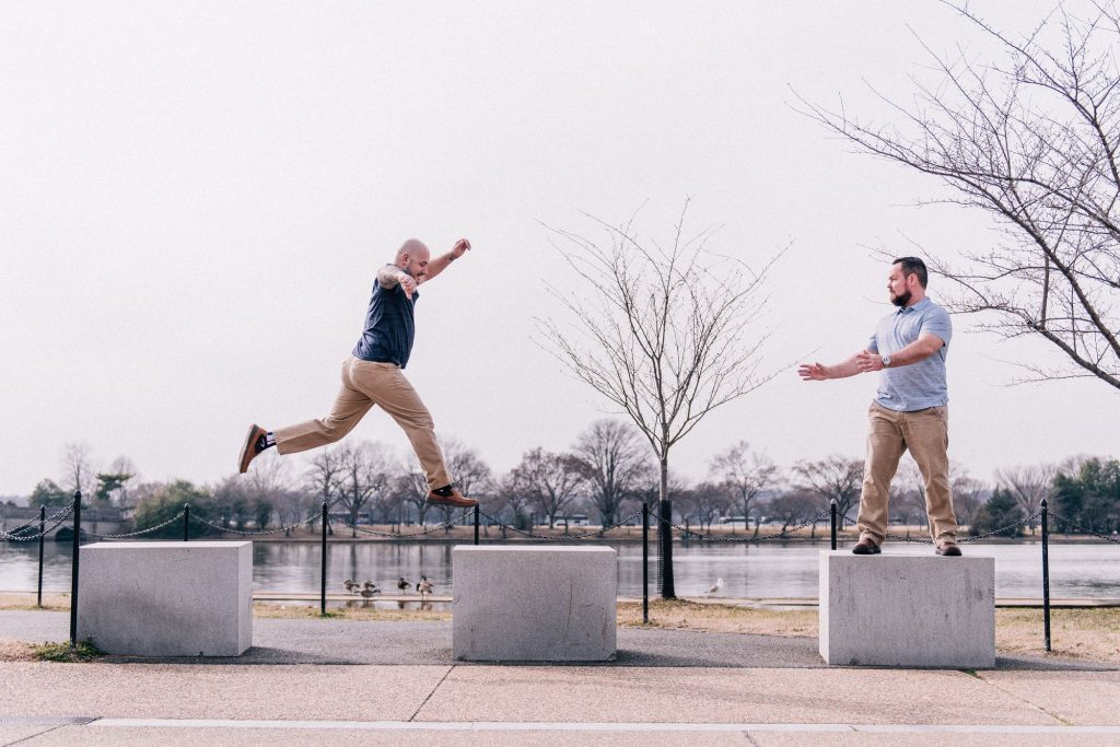 Funny jumping gay engagement shoot on the National Mall in Washington, DC.