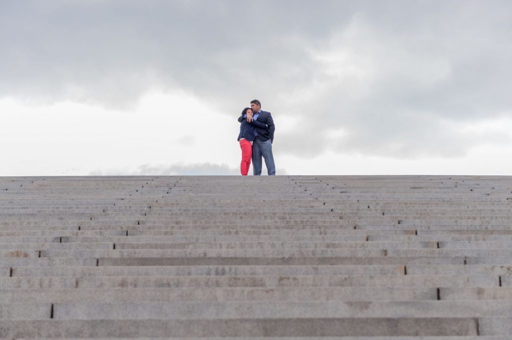 Indian engagement shoot with dramatic skies on the Watergate Steps near the Potomac River in Washington, DC